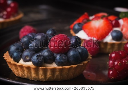 Berry mini tarts on a vintage metal tray with variety of blueberries, strawberries, raspberries and red currant - stock photo