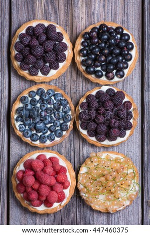 Berry mini tarts on the wooden table, top view.