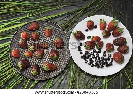 Berry on the black and white plates - stock photo