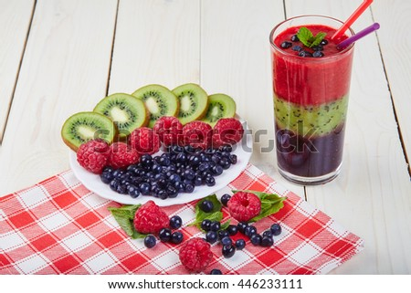 Berry smoothie.Fresh summer cocktail.Blueberry,raspberry,kiwi.Vitamin A. Vitamin C.Checkered napkin.On white wooden table with ingredients.Healthy lifestyle.Diet and weight loss concept. - stock photo