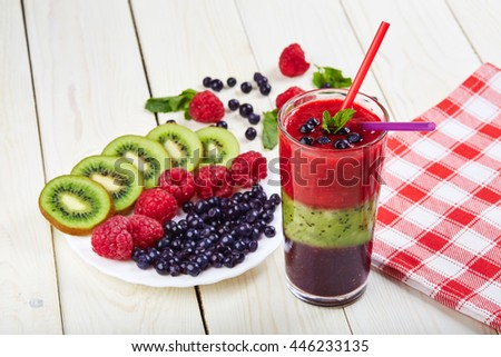 Berry smoothie.Fresh summer cocktail.Blueberry,raspberry,kiwi.Vitamin A. Vitamin C.Checkered napkin.On white wooden table with ingredients.Healthy lifestyle.Diet and weight loss concept.Top view - stock photo