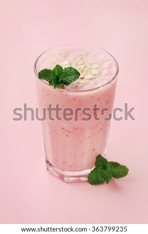 Berry smoothie or milkshake with oats decorated mint leaves on pink background, healthy and delicious breakfast