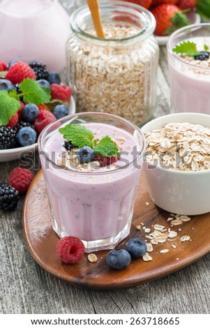berry smoothie with oatmeal in a glass on table, vertical, top view - stock photo