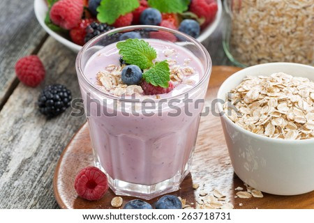 berry smoothie with oatmeal in a glass on wooden table, close-up, horizontal - stock photo