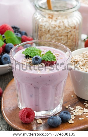 berry smoothie with oatmeal in a glass on wooden table, vertical, close-up, top view - stock photo