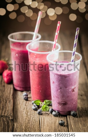 Berry smoothies with farm fresh blueberries and strawberries blended with yogurt and ice cream for a healthy summer treat with a bokeh of sparkling party lights - stock photo