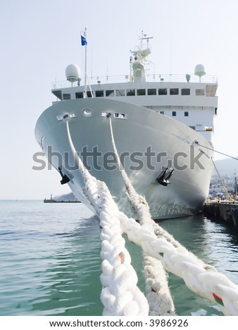 Berthing ropes on a pier with the big ship - stock photo