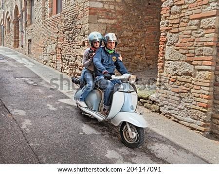 "BERTINORO (FC) ITALY - JUNE 14: a couple riding a vintage scooter Lambretta during the italian scooters rally ""Innocenti Day"" of Lambretta club Umbria, on June 14, 2014 in Bertinoro (FC) Italy   - stock photo"