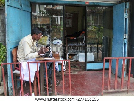 BERUWALA, SRI LANKA - NOVEMBER 13, 2014. A man sewing in a small tailor shop, industrial sewing machine in Beruwala, Sri Lanka. Sri Lankan private sewing industry. - stock photo