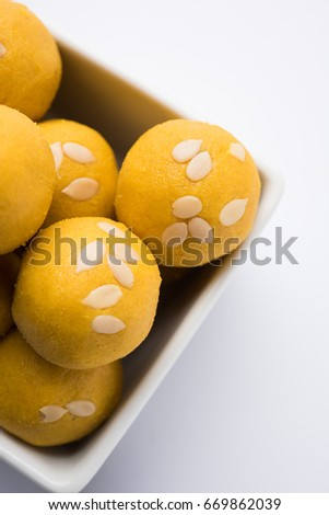 "Besan (gram flour) laddoos, an Indian sweet food  ""Besan Laddu"", served in a bowl over white background, selective focus"