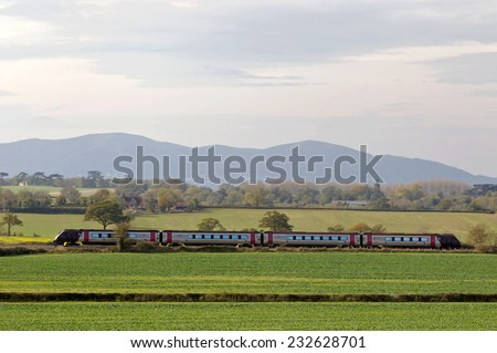 BESFORD, UK - OCTOBER 28: A Cross Country train heads northward past the Malvern hills on October 28, 2014 in Besford. Cross Country operate a fleet of 96 rail sets over 119 stations  - stock photo