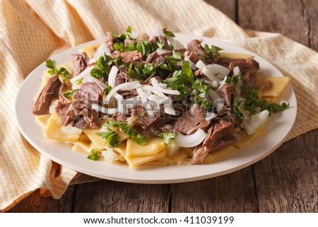 Beshbarmak dish: noodles with lamb and onion close-up on a plate on the table. horizontal - stock photo