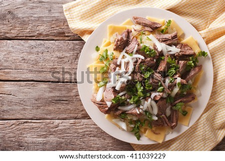 Beshbarmak dish: noodles with lamb and onion close-up on a plate on the table. horizontal top view - stock photo