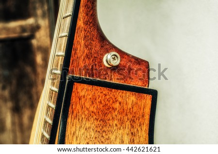 Beside Acoustic guitar resting against a blank grunge background with copy space - stock photo