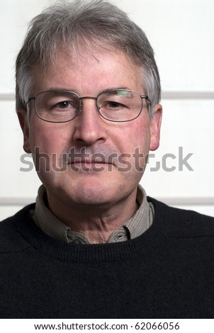 Bespectacled man in middle fifties wearing black sweater. - stock photo