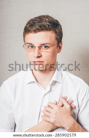 bespectacled man swears and keeps his hands on the heart - stock photo