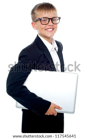Bespectacled young boy carrying a laptop tucked under his arm isolated against white background - stock photo