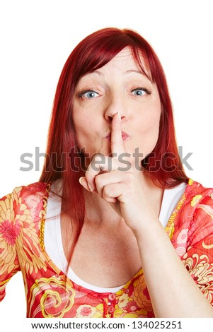 Best ager woman putting index finger on her lips - stock photo
