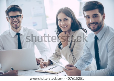 Best business team. Group of cheerful coworkers looking at camera with smile while sitting at the office table   - stock photo