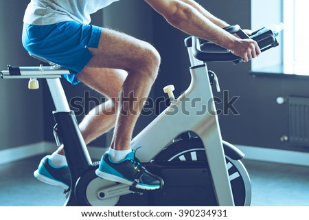 Best cardio workout. Side view part of young man in sportswear cycling at gym - stock photo