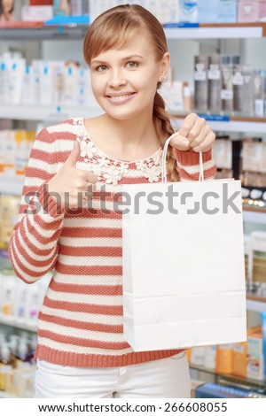 Best choice of medicines. Young cheerful woman shows thumbs up holding a paper bag copyspace in a pharmacy shop - stock photo