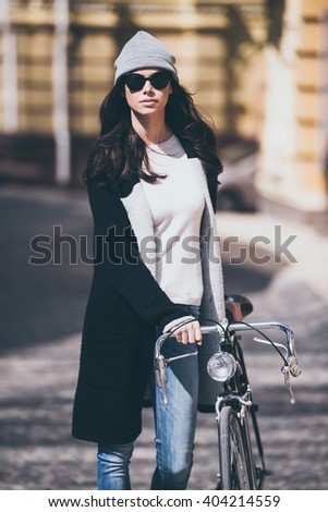 Best city transport. Beautiful young woman in sunglasses rolling her bicycle and looking at camera while walking outdoors