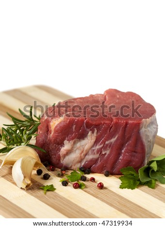 Best cut of raw beef filet steak, with garlic cloves, peppercorns and herbs. - stock photo