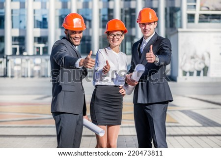 Best deal on a construction site. Three confident business architect in protective helmet standing on the site and keep the blueprints in hand and show a thumbs up - stock photo