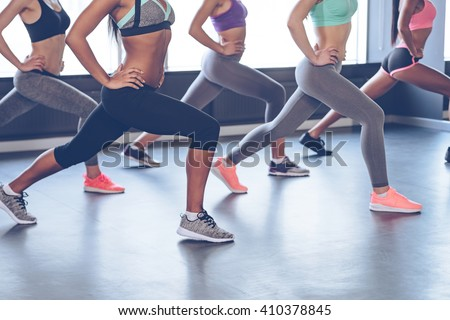 Best exercise for your booty. Side view part of young women with perfect buttocks in sportswear exercising while standing in front of window at gym - stock photo