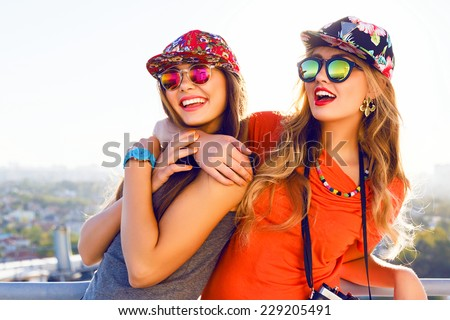 Best friend having fun on the roof, going crazy together, wearing floral swag hats and mirrored sunglasses, amazing view on the city, bright colors evening sunlight. - stock photo