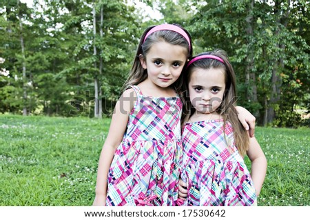 Best Friends and sisters  looking as if they might be up to something.  They are beautiful little girls with sweet expressions.   They have brown hair and brown eyes. - stock photo