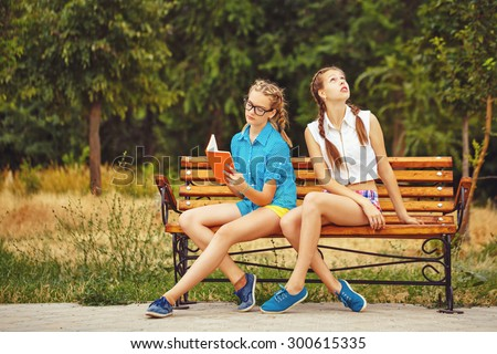 Best friends are reading diary sitting on a bench in a summer park. Teen girl dressed in shorts and a shirt. On summer vacation. The concept of true friendship. - stock photo