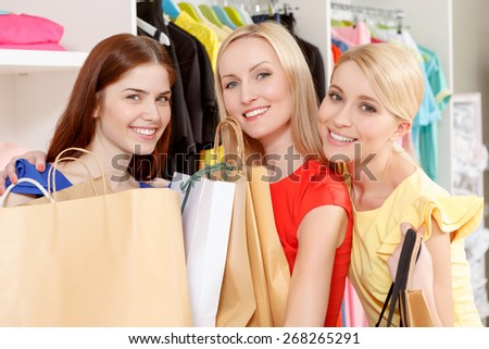Best friends at shopping. Three smiling girls looking at a camera holding paper bags copyspace in their hands