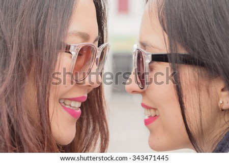 best friends - 2 beautiful trendy multi ethnic girls with smiling faces closely looking at their eyes, friendship fun happiness and playful attitude concept - stock photo