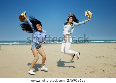 best friends cheerful happy girls enjoy freedom jumping dancing and playing on beach on a bright sunny day with very positive attitude  - stock photo