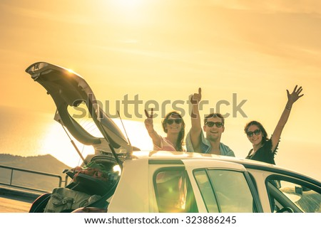 Best friends cheering by car road trip at sunset - Group of happy people outdoor on vacation tour - Friendship concept at travel with positive nostalgic emotions - Soft focus due to backlight contrast - stock photo