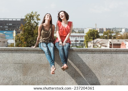 Best friends. Emotional portraits of beautiful brunettes. Pleasant emotions, happy mood. Female friendship. City street