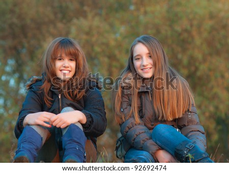 Best friends enjoying each others company in the nature on beautiful autumn day. - stock photo