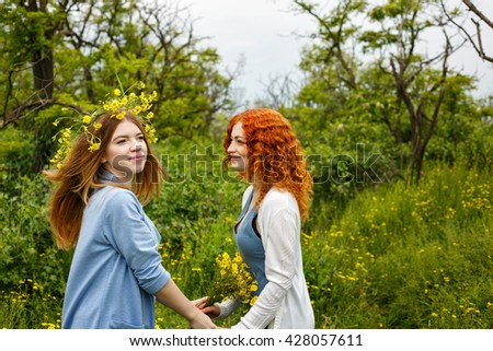 Best friends forever. Friends meet in the park. BFF. A girl holding a bouquet of wildflowers. A wreath of flowers on the head of the girl. Soft focus - stock photo