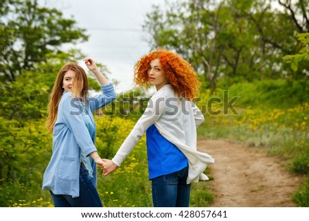 Best friends forever. Girlfriends strolling hand in hand in the park. BFF. Close friends. Gentle friendship. Soft focus - stock photo