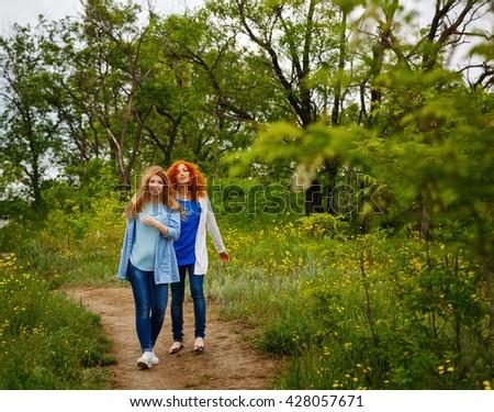 Best friends forever. Girlfriends walking in the park. BFF. Close friends. Gentle friendship. Soft focus - stock photo