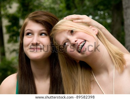 best friends forever - two pretty teenage girls, age 13, being happy and close - stock photo