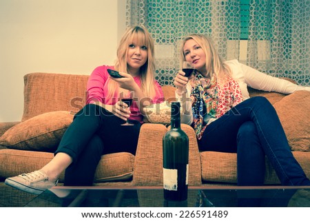 best friends - 2 girls enjoy watching tv at home drinking a glass of wine retro style filtered stock photo - stock photo