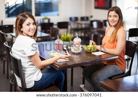 Best friends hanging out and eating a healthy lunch at a restaurant - stock photo