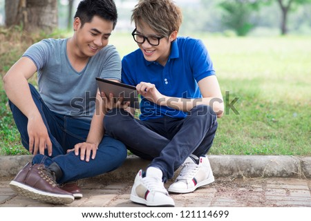 Best friends hanging out together watching stuff on the tablet screen - stock photo