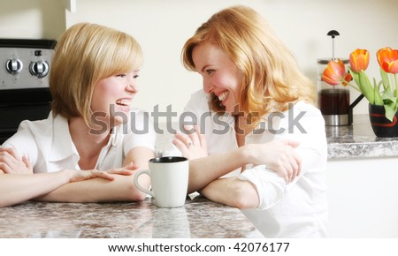 best friends having a laugh in the kitchen - stock photo