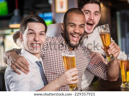 Best friends in a bar. Men shout and rejoice in meeting and drink beer. Three other men drinking beer and having fun together in the bar - stock photo
