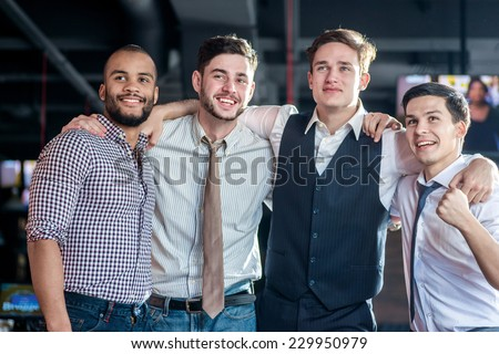 Best Friends in the bar. Four friends standing arm in arm at the bar and look at the TV - stock photo