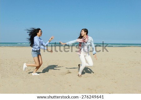 best friends 2 interracial girl friends playing on a sunny beach smiling and enjoying the sunshine - stock photo