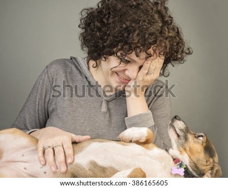 Best friends/Pretty stylish young woman rubbing the stomach of small, mixed breed dog - stock photo